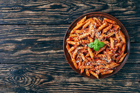 classic italian penne arrabiata  in a clay bowl with basil and freshly grated peccorino cheese on a rustic wooden table, view from above, flatlay, copy space for text left Фото со стока