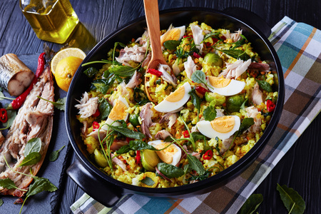 delicious Kedgeree with flaked smoked fish, hard boiled eggs, rice, kale, brussel sprouts, spices and herbs in a dutch oven on a black wooden table with ingredients, top view