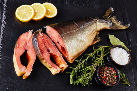 close-up of smoked wild salmon cut in steaks with fresh rosemary salt and peppercorn on a black slate plate, view from above Standard-Bild - 114796880