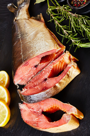 smoked wild salmon cut in steaks with fresh rosemary salt and peppercorn on a black slate plate, vertical view from above, close-up Standard-Bild - 114796883