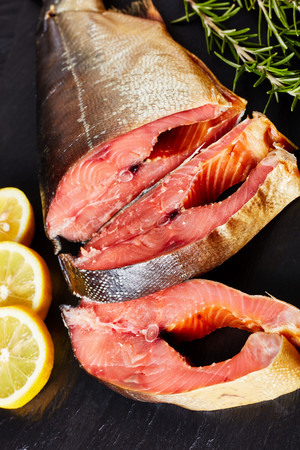 smoked wild salmon cut in steaks with fresh rosemary salt and peppercorn on a black slate plate, vertical view from above, close-up Standard-Bild - 114796884