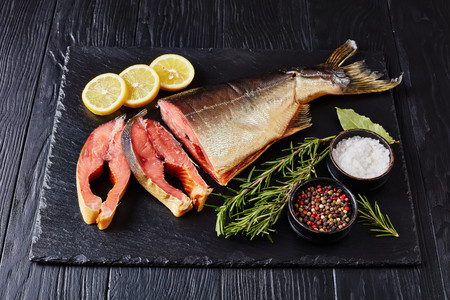 wild salmon cut in steaks with fresh rosemary salt, bay leaves and peppercorns on a black stone tray, view from above Standard-Bild - 114796886