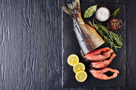 wild salmon cut in steaks with fresh rosemary salt and peppercorn on a black stone tray, view from above, close-up, flat lay, copy space Standard-Bild - 114796887