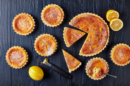 delicious Swiss Easter Rice Tarts sprinkled with powdered sugar and lemon zest, gateau de Paques, Osterfladen in tart shells, on a black wooden table with lemon, horizontal view from above, flat lay Standard-Bild - 114796888