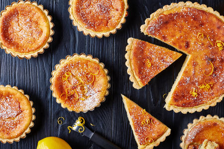 Swiss Easter dessert - semolina Tarts sprinkled with powdered sugar and lemon zest, gateau de Paques, Osterfladen, on a black table with lemon, horizontal view from above, flat lay, close-up Standard-Bild - 114796890