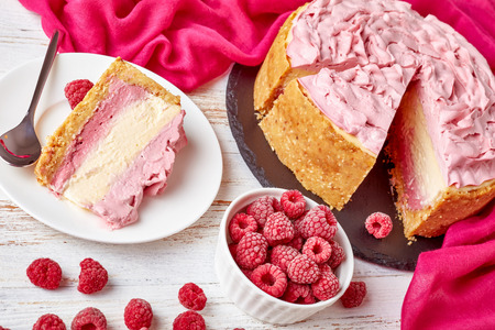 portion of a white chocolate raspberry cheesecake on a plate and sliced cheesecake on a black stone tray with cloth and frozen raspberries on a white wooden table, view from above, close-up Standard-Bild - 114884054