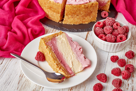 close-up of a portion of a layered raspberry cheesecake on a plate. sliced cheesecake on a black stone tray with cloth and frozen raspberries on a white wooden table, view from above Standard-Bild - 114884057