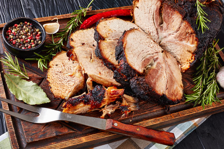 overhead view of slow roasted tender pork ham on a wooden chopping board with rosemary, garlic, peppercorns, and fork, view from above Standard-Bild - 115071625