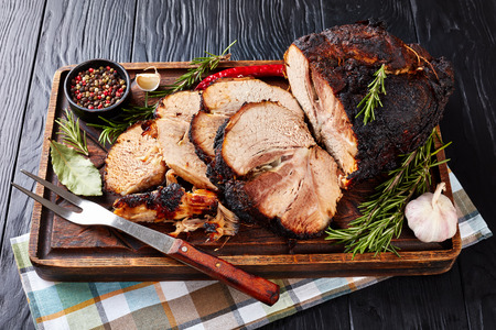 overhead view of slow roasted tender pork ham on a wooden chopping board with rosemary, garlic, peppercorns, and fork, view from above Standard-Bild - 115071622
