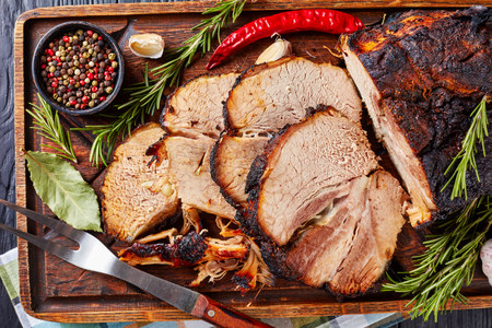 overhead view of sliced Roasted pork ham on a wooden board with rosemary, garlic, peppercorns, and fork, view from above, flatlay, close-up, macro Standard-Bild - 115071628