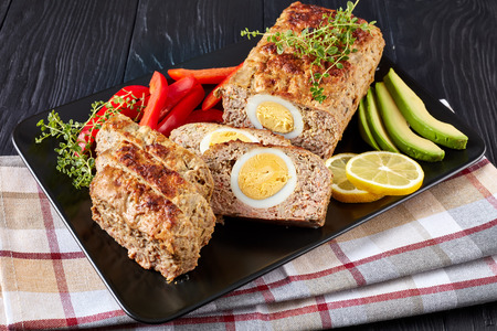 Meatloaf Bolo de Carne Alemao served with red pepper and avocado slices on a black rectangular platter on a wooden table, vertical view from above