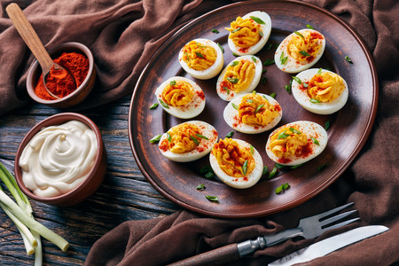 close-up of Deviled Eggs sprinkled with paprika and finely chopped green onion on an earthenware plate on an old rustic wooden table with brown cloth, view from above