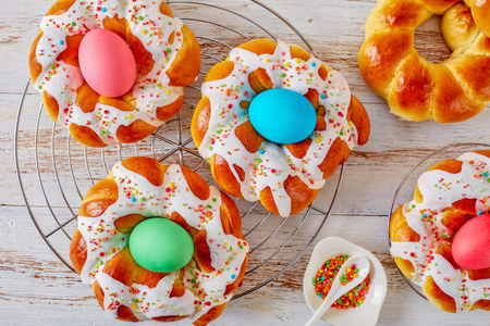 homemade sweet Italian Easter Bread Rings glazed around dyed egg and topped with colorful sprinkles on a wire rack, on an old white wooden table, view from above, flatlay