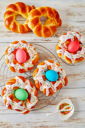 Italian Easter Bread Rings glazed around dyed egg and topped with colorful sprinkles on a wire rack, on an old white wooden table, vertical view from above Stock Photo