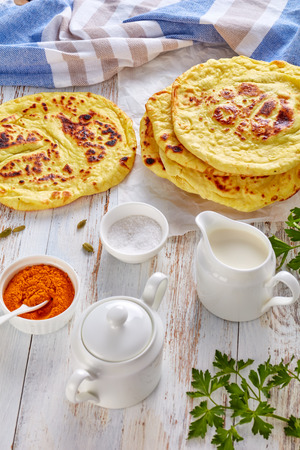 naan - delicious hot freshly baked indian flatbread on a white table with ingredients and stack of flatbreads at the background, vertical view from above, close-up