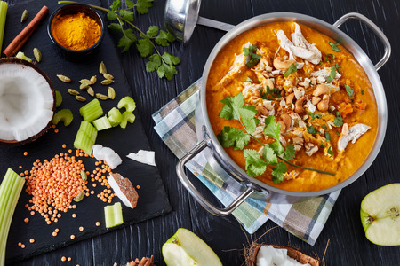 overhead view of hearty Mulligatawny soup in a metal casserole on a black wooden table with a soup ladle and ingredients,  traditional Indian and english cuisine, view from above, flatlay, close-up