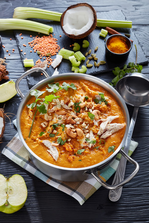 hearty spicy Mulligatawny soup with chicken meat sprinkled with fried cashew in a metal pot on a black wooden table,  Indian and english cuisine, vertical view from above