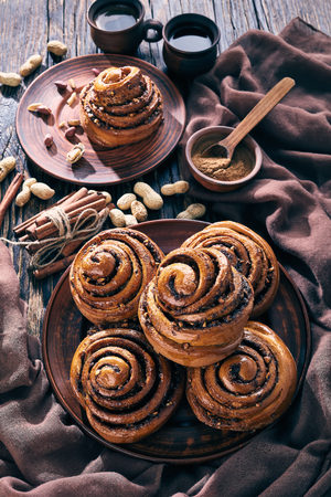freshly baked Cinnamon rolls buns with peanuts served on a earthenware plate and two cups of coffee on an old wooden table. Kanelbulle swedish dessert, vertical view from above Foto de archivo