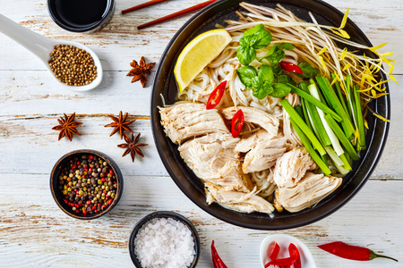 soup Pho Ga with chicken breast, rice noodles, bean sprouts, spices and fresh herbs in an earthenware bowl, vietnamese cuisine, view from above, flatlay, close-up