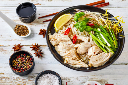 soup Pho Ga with chicken breast, rice noodles, bean sprouts, spices and fresh herbs in an earthenware bowl, vietnamese cuisine, view from above