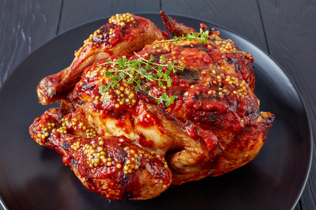Herb-Roasted Chicken smothered with Tomato sauce and whole grain mustard on a black plate, view from above, close-up