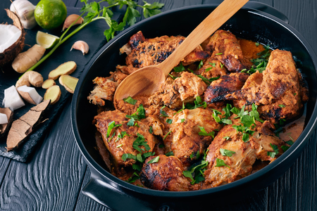 Kuku Paka, Kenyan chargrilled Chicken stewed in creamy spicy Coconut Sauce served in earthenware saucepan on a wooden table. ingredients on a stone cutting board, view from above, close-up Stock Photo