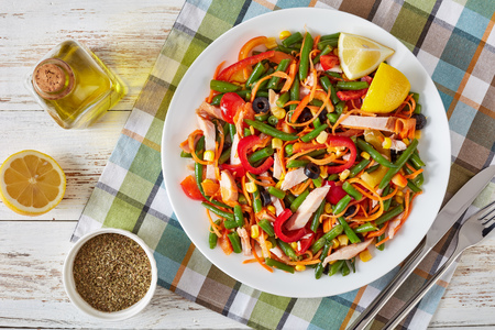 overhead view of mexican style healthy salad with green bean, sweet pepper, black olives, carrot, corn and ham cut in strips on a white plate on a rustic table with napkin and cutlery, close-up