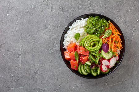 Raw Organic Ahi salmon Poke Bowl with rice, seaweed, avocado rose, radish, carrot, cucumber and green salad, sprinkled with spring onion and sesame seeds, view from above, flatlay Imagens