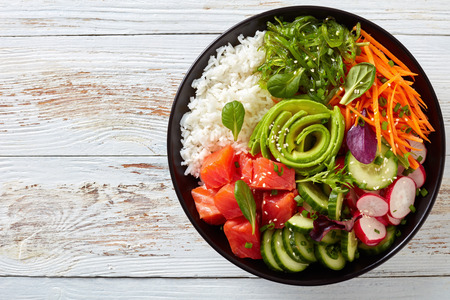 Raw Organic Ahi salmon Poke Bowl with rice, seaweed, avocado rose, radish, carrot, cucumber and green salad, sprinkled with spring onion and sesame seeds, view from above, flatlay Stock Photo