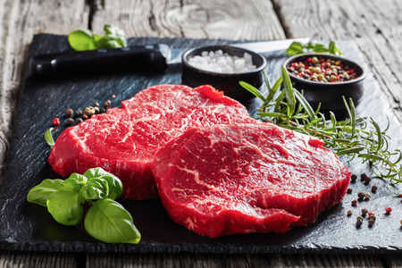 raw beef steaks with peppercorns, fresh basil leaves, rosemary, salt and knife on a black slate plate on an old rustic wooden table, horizontal view from above, close-up Stok Fotoğraf