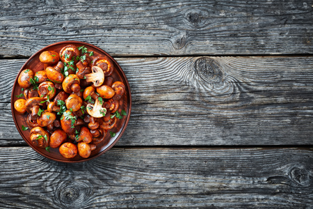 overhead view of delicious lightly fried champignons, Champinones Al Ajillo, Spanish Garlic paprika Mushrooms on an earthenware plate on an old rustic wooden table, traditional spain tapas, flatlay Reklamní fotografie