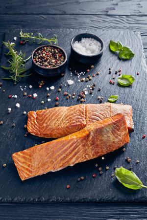 baked salmon fillet with aromatic herbs, spices on a slate plate on a black wooden kitchen table, vertical view from above