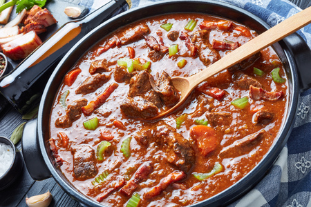 traditional irish beef and beer stew with carrots, celery stalk, carrots and spices in a dutch oven with ingredients and bottle with beer on a black wooden table, view from above,  close-up