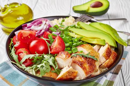 insalata di pollo alla griglia in una ciotola con couscous al vapore, verdure fresche, avocado, scalogno e rucola su un tavolo di legno bianco con olio di sesamo, vista dall'alto, primo piano