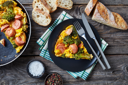 omelette with broccoli and sausages in a skillet and served on a plate on an old grey rustic wooden table with sliced crusty whole grain French baguette, view from above, flat lay, close-up