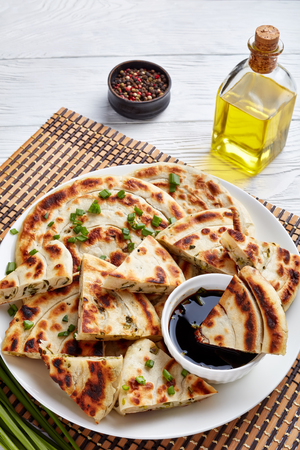 Hot Chinese green onion Pancakes cut in triangle slices on a plate and served with soy sauce dipping, vertical view from above Stock Photo
