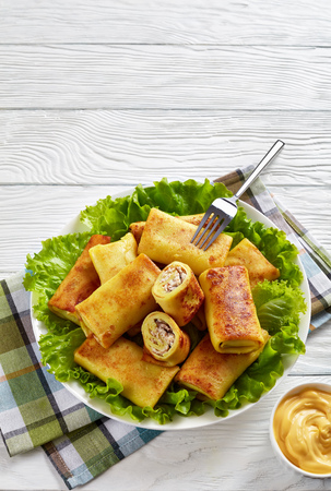 crepe rolls with ground chicken meat and mushrooms filling served on a bad of fresh lettuce leaves on a white plate on a wooden table with cheese sauce, vertical view from above, close-up Stock Photo
