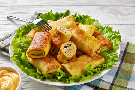 close-up of Savory crepe rolls with ground chicken meat and mushrooms filling served on a bad of fresh lettuce leaves on a white plate on a wooden table with cheese sauce, view from above Stock Photo