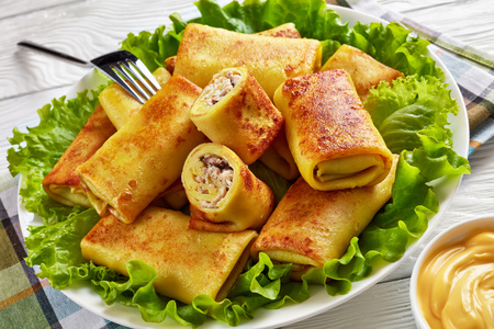 close-up of Savory crepe rolls with ground chicken meat and champignon filling served on a bad of fresh lettuce leaves on a white plate on a wooden table with cheese sauce