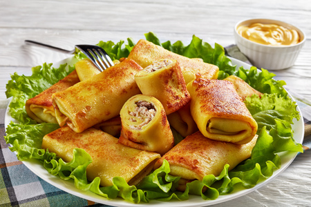 close-up of Savory crepe rolls with ground chicken meat and champignon filling served on a bad of fresh lettuce leaves on a white plate on a wooden table with cheese sauce at the background Stock Photo