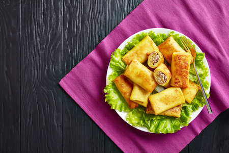 overhead view of Savory crepe rolls with ground chicken meat and champignon filling served on a bad of fresh lettuce leaves on a white plate on a black wooden table, flatlay