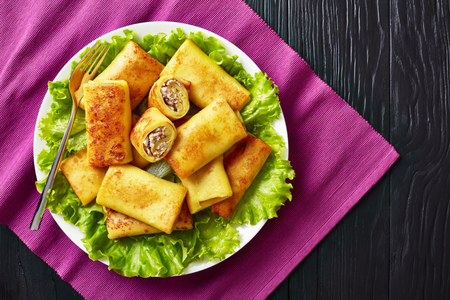 overhead view of Savory crepe rolls with ground chicken meat and champignon filling served on a bad of fresh lettuce leaves on a white plate on a black wooden table, flatlay, copy space, close-up