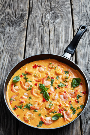 creamy Shrimps in Coconut Sauce with blended vegetables and herbs, camarao no leite de coco, brazilian recipe, vertical view from above, close-up