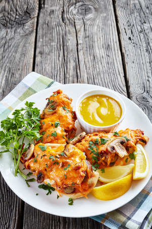 aussie chicken breasts topped with mushrooms, bacon and cheddar cheese cooked in a honey-mustard sauce served on a white plate with lemon mustard dipping, view from above, close-up Stock Photo