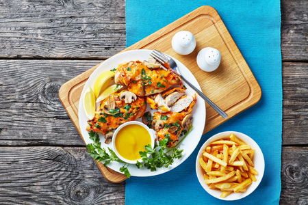 aussie chicken breasts topped with mushrooms, bacon and melted cheese cooked in a honey-mustard sauce served on a white plate with lemon mustard dipping and french fries, view from above, flatlay