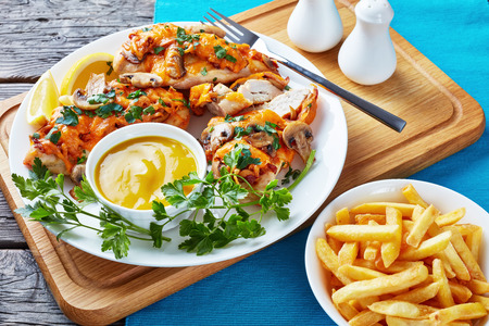close-up of aussie chicken breasts topped with mushrooms, bacon and melted cheese cooked in a honey-mustard sauce served on a white plate with lemon mustard dipping and french fries