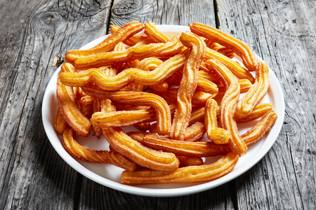 close-up of churros - traditional spanish and mexican dessert on a white platter on an old grey rustic wooden table, view from above