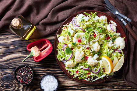 Cauliflower salad with shredded cabbage, bell pepper, red onion and fresh mint on an  earthenware plate on a rustic wooden table with brown cloth, horizontal view from above, flatlay