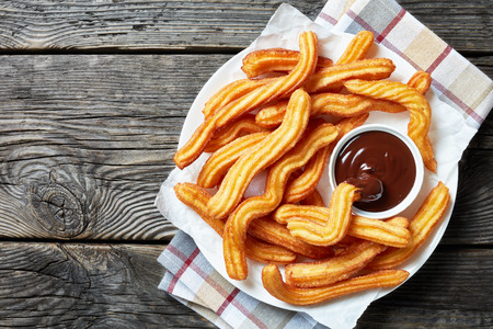 churros - Traditional Spanish and Mexican dessert on a white plate with chocolate sauce on an old grey rustic wooden table, horizontal view from above, close-up, flatlay Фото со стока