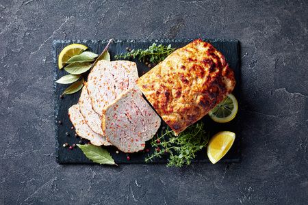 close-up of sliced chicken meatloaf on a black slate flat plate with lemon slices and fresh thyme on a concrete table, view from above, flatlay Imagens